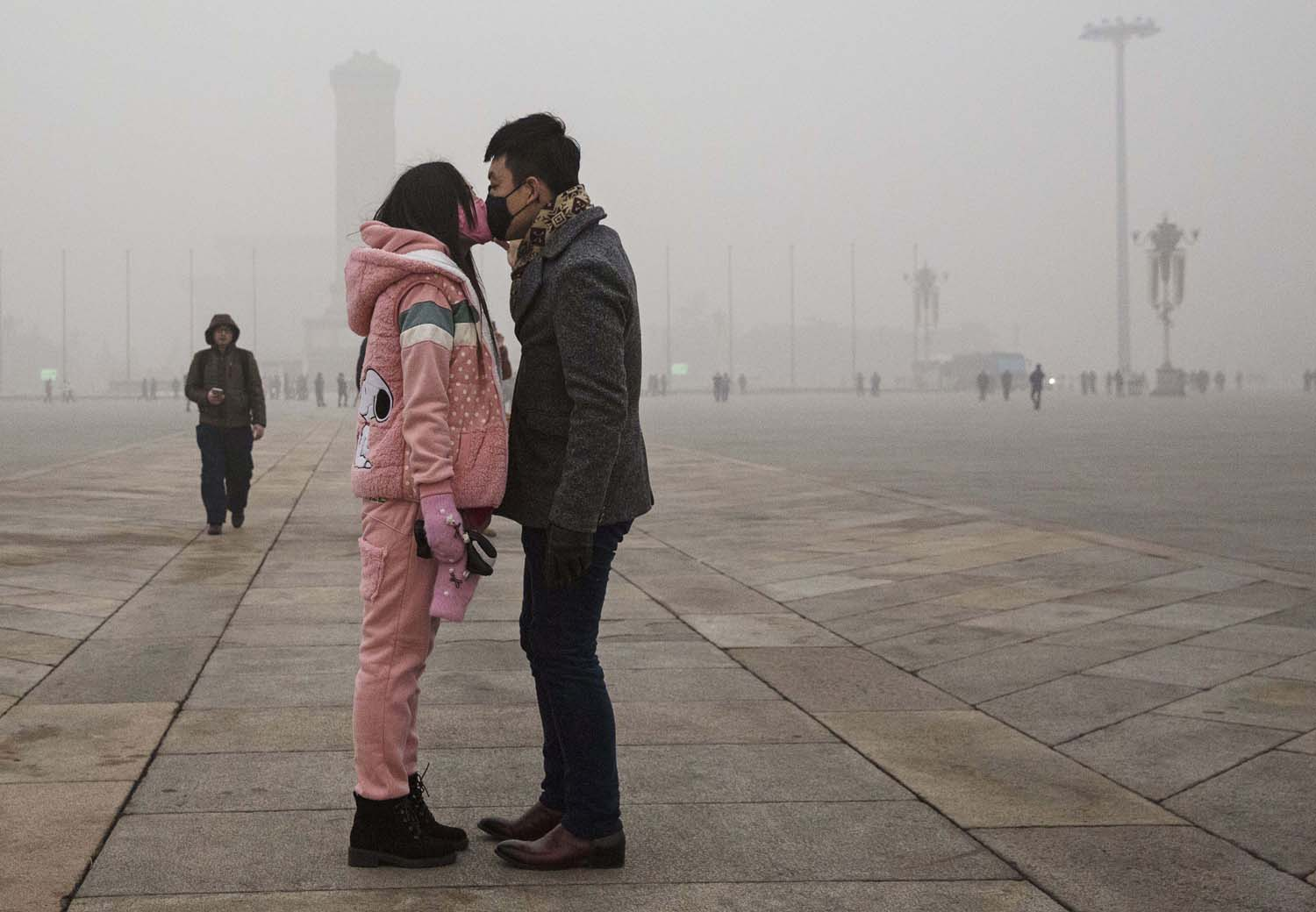 Curiosamente, en este beso los labios no se tocan, debido a la polución. La foto fue tomada en Pekín, durante el reciente pico de contaminación que puso en alerta a la capital de China y a otras urbes alrededor. Foto: KEVIN FRAYER/GETTY IMAGES