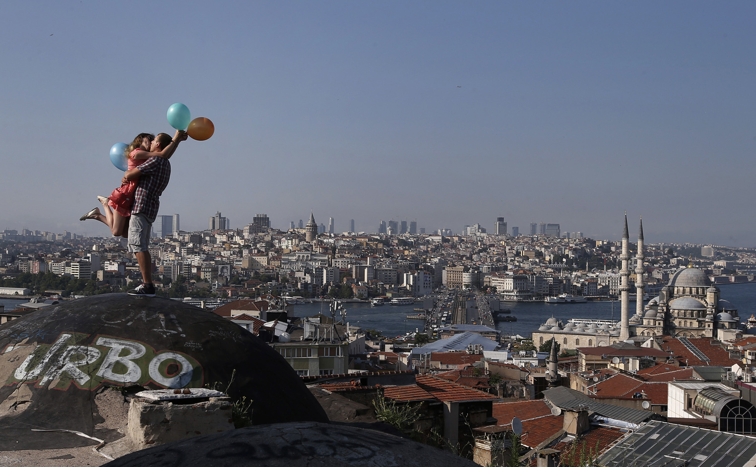 09 Jul 2015, Istanbul, Turkey --- A couple kiss each other as they pose for a friend taking photographs, backdropped by Istanbul's skyline, Thursday, July 9, 2015. Istanbul is a thoroughly modern place, but it traces its roots back to 660 B.C. It's the former seat of the opulent Byzantine and Ottoman empires and is divided into European and Asian sides by the Bosphorus Strait, offering a wealth of history and stunning scenery. (AP Photo/Emrah Gurel) --- Image by © Emrah Gurel/AP/Corbis